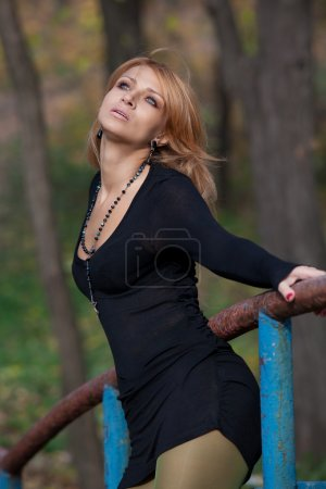 Attractive slender blonde woman gracefully bent holding the rail