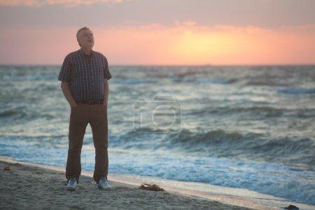 Photo pour L'homme se tient sur la plage et regarde le soleil se lever à travers les nuages à l'horizon de la mer - image libre de droit