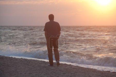 Photo pour Homme marchant sur la plage et regardant le soleil se lever à travers les nuages à l'horizon de la mer - image libre de droit