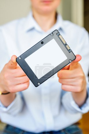 Woman holding fast SSD Solid State Drive