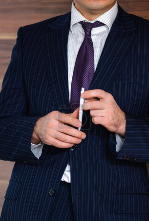 Photo pour Homme d'affaires confiant portrait exécutif tenant stylo blanc dans les mains couché à côté du mur en bois de luxe dans son bureau moderne - image libre de droit