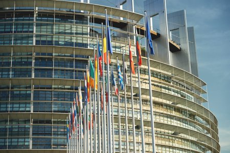 Photo for Side view of all members European Union flags waving in front of European Parliament building on a beautiful morning - Royalty Free Image