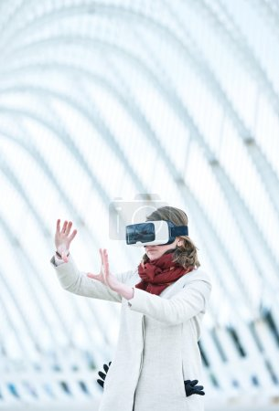 Photo for Woman wearing a virtual reality headset, controlling the experience with hand gesture - touching and controling immaginare surfaces - Royalty Free Image