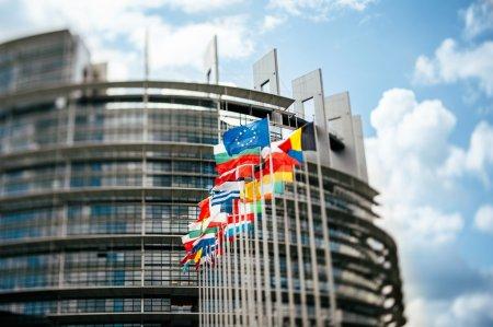 Photo pour Drapeaux devant le Parlement européen, drapeaux devant le Parlement européen, Strasbourg, Alsace, France. Objectif Tilt shift utilisé pour accentuer les drapeaux s et sublime filtre tonique appliqué pour un effet plus naturel - image libre de droit