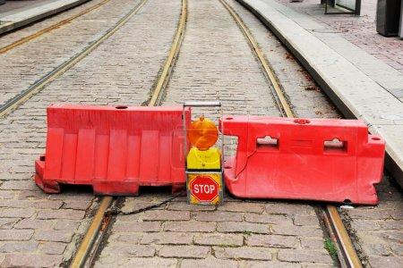 Foto de Road closed STOP sign and two red symbol barrier over a tramway track. - Imagen libre de derechos