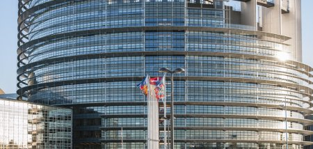 Photo for Frontal view of The European Parliament building in Strasbourg, France with flags waving on a spring evening - Royalty Free Image