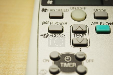 Modern air conditioning remote control on wooden table