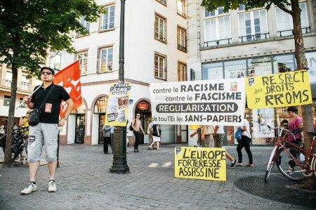 Photo pour Personnes protestant contre la politique d'immigration et la gestion des frontières qui demandent un engagement à la suite de catastrophes maritimes de migrants - homme protestant avec des pancartes et un drapeau - image libre de droit