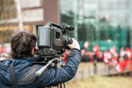 Caméraman travaillant à l'extérieur lors de rupture d'actualité live