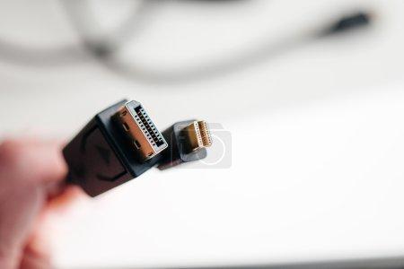 Hand holding Mini DisplayPort and DisplayPort cables