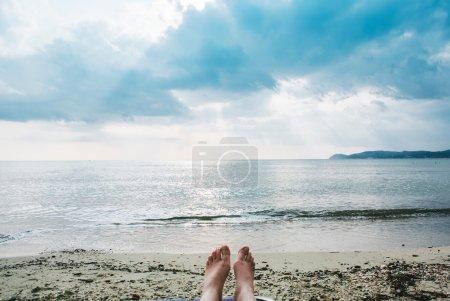 Female legs and feet sunbathing on beach