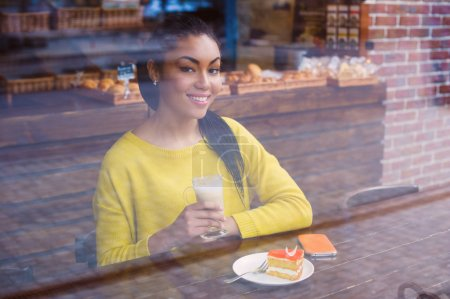 Mixed race girl with coffee view through the window