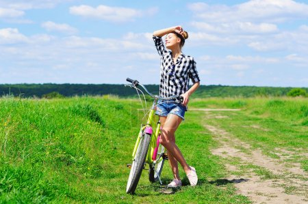 Photo for Young woman standing next to her bike facing the sun - Royalty Free Image