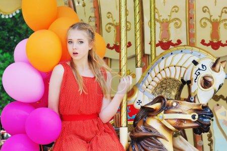 Jeune femme modèle chevauchant un carrousel
