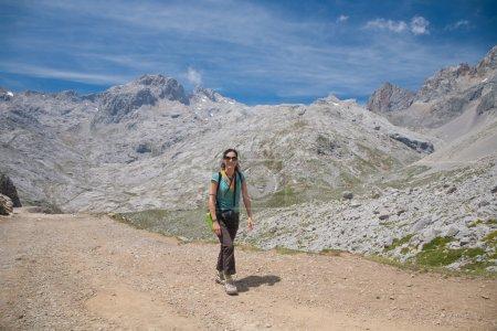 Photo pour Femme heureuse souriante de sport brunette avec un pantalon chemise verte marron marche ou randonnée pédestre ou randonnée sur le chemin rural dans les montagnes de Picos de Europa en Cantabrie Espagne - image libre de droit