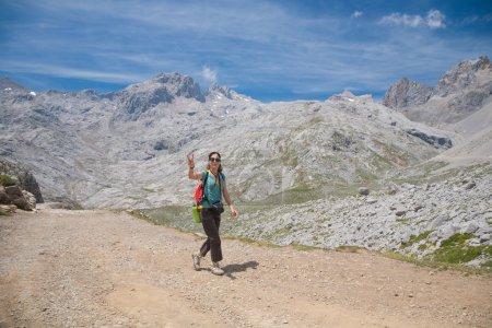 Photo pour Femme brune sport avec un pantalon chemise verte marron marche ou randonnée pédestre ou randonnée sur le chemin rural dans les montagnes de Picos de Europa en gesticulant symbole de victoire Espagne Cantabrie avec doigt mains - image libre de droit