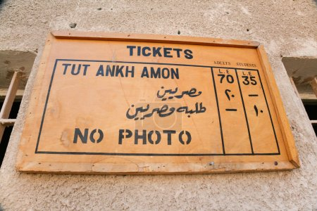 Wooden placard with rates, tickets and no photo, i...
