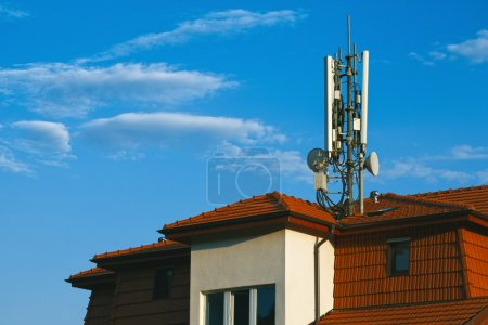 Living building with GSM antennas on roof isolated on blue sky