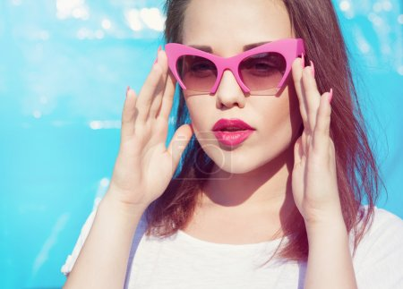 Colorful portrait of young attractive woman wearing sunglasses.
