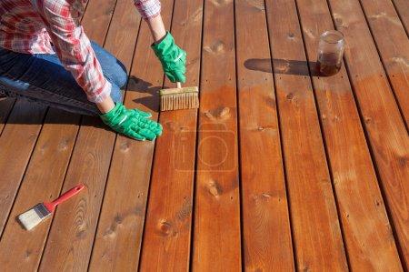 Woman applying protective varnish on a floor