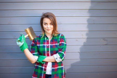 Young working woman with paint brush