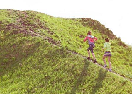 Photo pour Deux jeunes amies en forme faisant de l'exercice dans un parc en haut de la colline. Style de vie sain actif et concept d'entraînement en plein air - image libre de droit