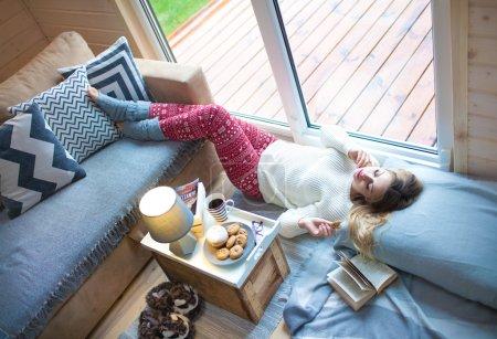 Photo pour Jeune belle femme blonde avec une tasse de café allongé à la maison relaxant par la fenêtre livre de lecture. Il pleut dehors. Lazy day off concept . - image libre de droit