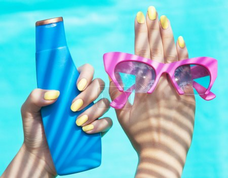 Woman holding sunglasses and sunscreen lotion
