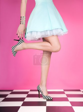 Photo for Young woman standing on one leg wearing high heels - Royalty Free Image