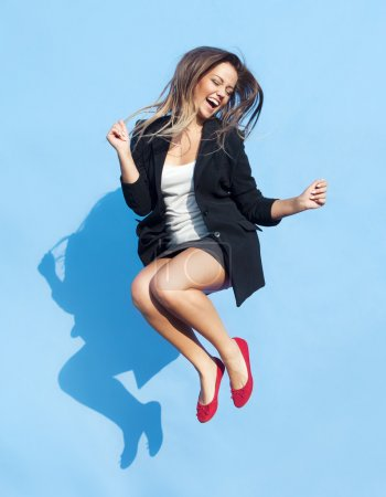 Photo for Successful young attractive laughing woman jumping up - Royalty Free Image