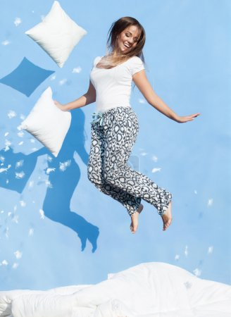 Photo for Happy morning concept, woman holding a pillow jumping up on bed - Royalty Free Image