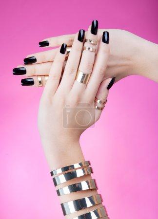 Photo pour Mains en gros plan de la jeune femme avec manucure noire portant bracelet en or et anneaux articulaires - image libre de droit