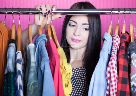 Photo for Time to refresh wardrobe young attractive disappointed woman searching for clothing in a closet - Royalty Free Image