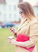 Young attractive woman using a smart phone in the street.