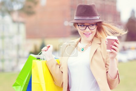Young attractive shopper woman wearing hat and glasses holding shopping bags