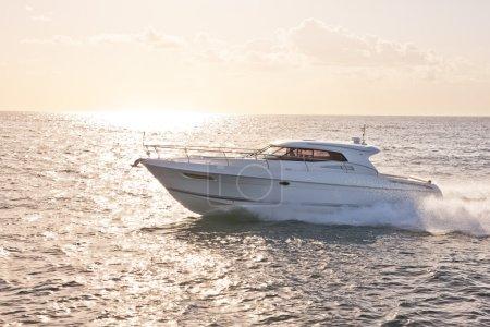 Motor boat in the ocean in evening sunlight
