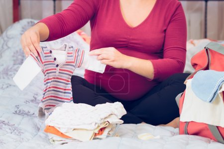 Photo for Pregnant woman packing hospital bag preparing for labor - Royalty Free Image