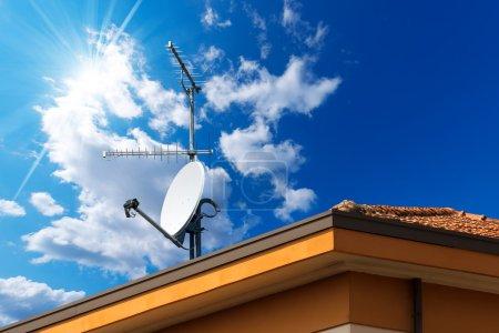 Photo pour Antennes antenne et tv par satellite sur le toit de la maison avec un beau ciel bleu - image libre de droit