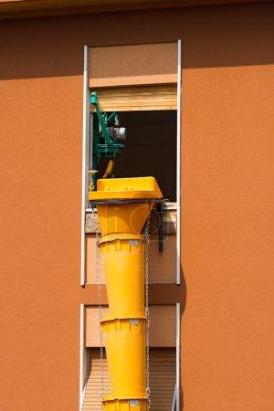 Photo pour Tuyau flexible en plastique jaune pour enlever les déchets de construction sur le chantier - image libre de droit