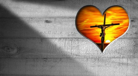Photo for Wooden grey background with a hole in the shape of heart with Jesus crucified and a beautiful sunset with cloudy sky - Royalty Free Image