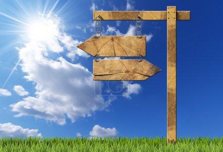 Photo pour Panneau directionnel en bois avec deux flèches vides dans la direction opposée suspendues avec une chaîne métallique sur un poteau en bois sur ciel bleu avec nuages, rayons du soleil et herbe verte - image libre de droit