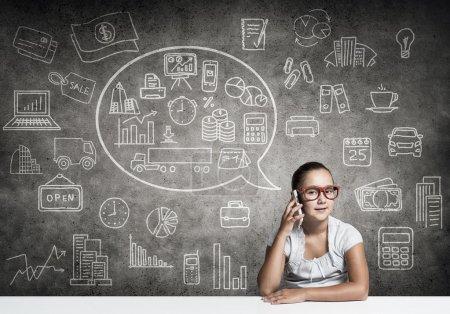 Photo pour Ecole fille en lunettes rouges assis à la table parler téléphone mobile - image libre de droit