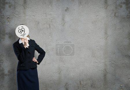 Businesswoman hiding her face behind mask
