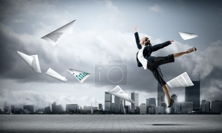 jumping businesswoman and papers