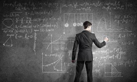 Photo pour Arrière vue homme enseignant en adapter les formules de physique permanent et dessin - image libre de droit