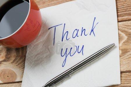 Photo pour La tasse à café plume et serviette avec message romantique écrite sur la serviette sur la table en bois - image libre de droit