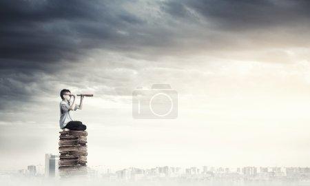 Kid on pile of books looking in spyglass