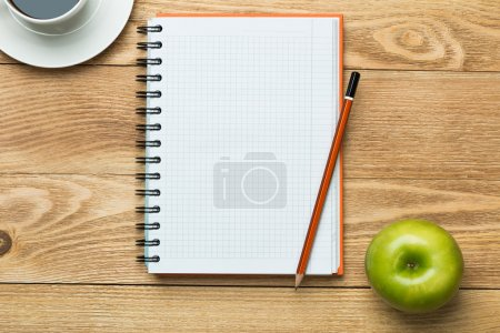 Photo for White blank notepad with cup of coffee and green apple on wooden table - Royalty Free Image