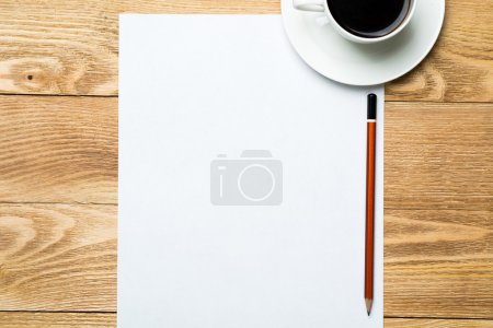 Photo for White blank paper sheet with cup of coffee on wooden table - Royalty Free Image