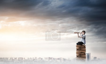 Kid of school age sitting on pile of books and loo...